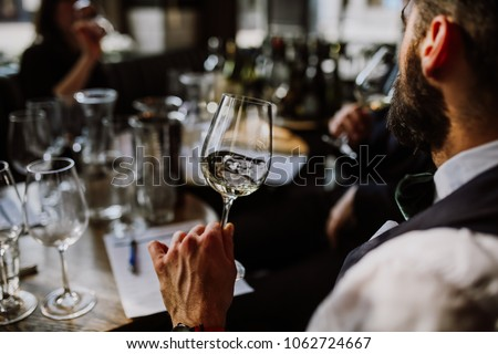 A young European man drinking white wine at the wine tasting. Selective focus point on the wine glass and the man. Other glasses and wine bottles in the background. #1062724667