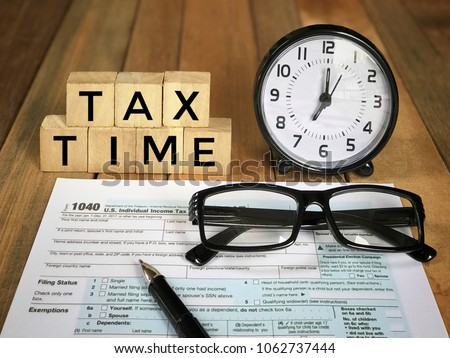 Tax-filling concept - 'Tax time' words on wooden blocks, pen, eyeglasses, featuring half of U.S IRS 1040 form. With vintage-styled background. #1062737444