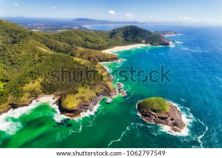 Scenic aerial view of colourful Australian pacific coast off Arakoon national park with tall hills cutting down to cliffy shore and beaches. #1062797549