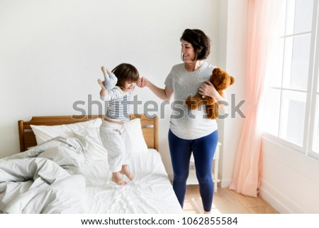 Pregnant mom spending time together with her daughter #1062855584