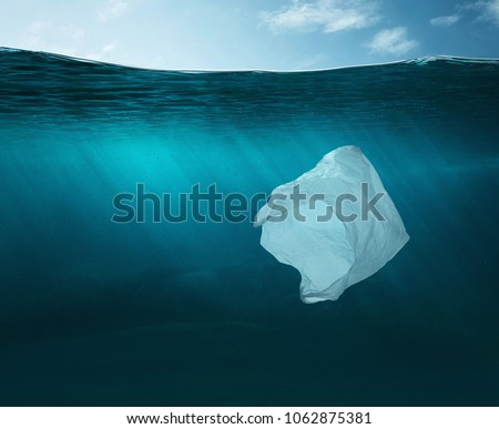 Pollution concept. Plastic bag floating in the ocean with copy space #1062875381