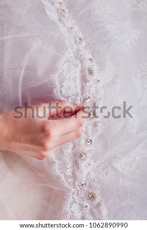 hands sewing a silk lace decorated with beads ribbon to the white fabric, decoration with beads, ribbon, wedding fashion designing #1062890990