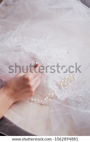 hands sewing beads pearls to the lace piece of fabric, making a wedding dress, decoration with pearls, emroidery with pearls on a lace #1062894881