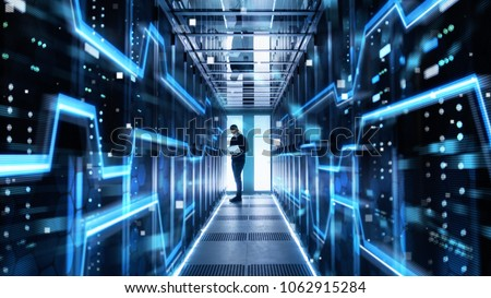 Male IT Engineer Works on a Laptop in a Big Data Center. Rows of Rack Servers with High Speed Internet Visualization. #1062915284