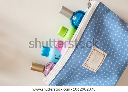 Blue travel toiletry bag with travel toiletries, small plastic bottles of hygiene products and perfume on white background.  Royalty-Free Stock Photo #1062982373
