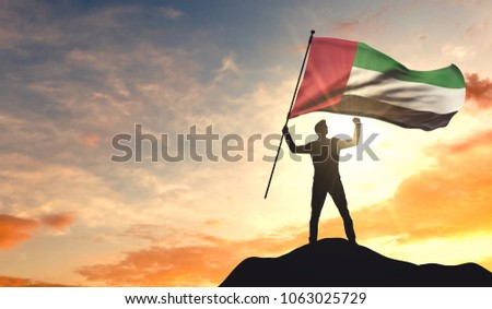 United Arab Emirates flag being waved by a man celebrating success at the top of a mountain. 3D Rendering #1063025729