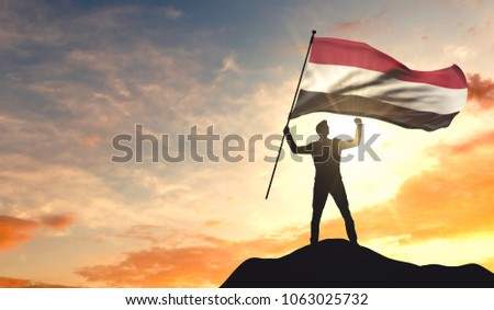 Yemen flag being waved by a man celebrating success at the top of a mountain. 3D Rendering #1063025732