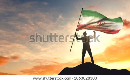 Iran flag being waved by a man celebrating success at the top of a mountain. 3D Rendering #1063028300