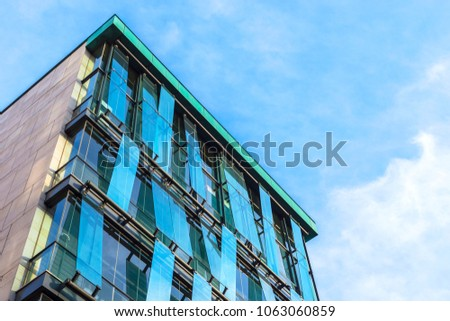 Glass facade of the building with a blue sky and white clouds #1063060859