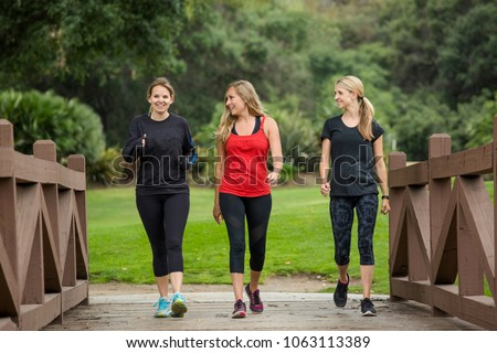 Group of women in their 30s walking together in the outdoors. Cute blond and fit women in their mid 30s who are active and working to stay healthy. Full length photo with copy space #1063113389
