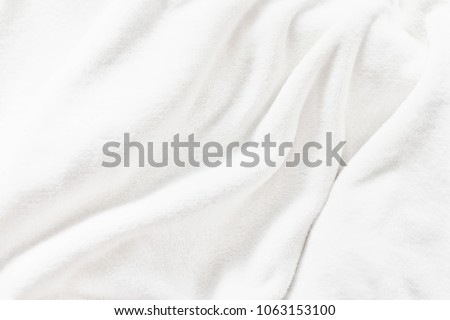 White soft wrinkle fleece synthetic cloth blanket texture background, wallpaper, backdrop. Space for text. #1063153100