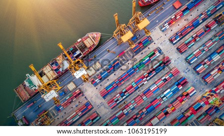 Logistics and transportation of Container Cargo ship and Cargo plane with working crane bridge in shipyard at sunrise, logistic import export and transport industry background Royalty-Free Stock Photo #1063195199