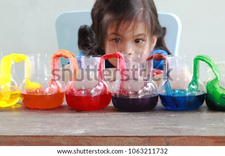 Fun and easy science.5 years old Asian girl making Walking Water experiment.Food color add to the water in the recycled bottle,water moving along the paper then color mixed.Concept of science for kid  #1063211732