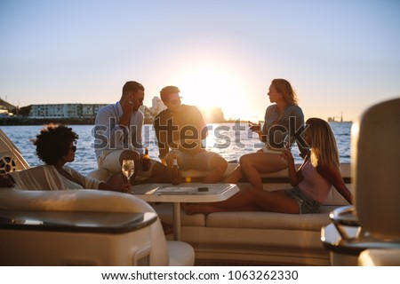Young rich friends drinking wine and beers in boat party during sunset. Group of young people partying on yacht. Royalty-Free Stock Photo #1063262330