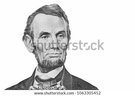 A piece of a money bill showing an important person is named  LINCOLN isolated on white background. Symbol of 5 dollars.