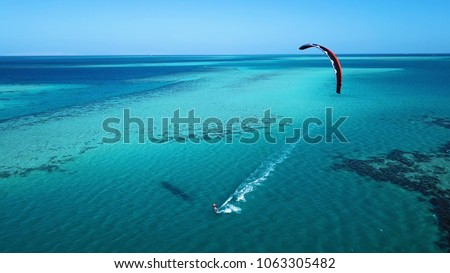 Aerial view. Kite surfing on the blue sea in the background of beautiful clouds #1063305482