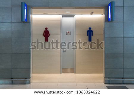 Front view of public restroom or toilet with man and women signs on marble wall. Way to clean restoom man and women toilet sign.