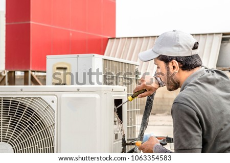 a professional electrician man is fixing a heavy duty unit of central air conditioning system by his tools on the roof top and wearing grey color of uniform and white cap #1063354583