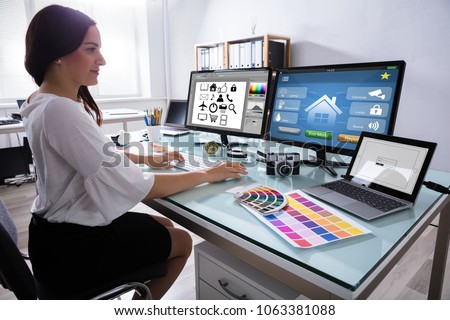 Close-up Of A Female Designer Working On Multiple Computer At Workplace #1063381088