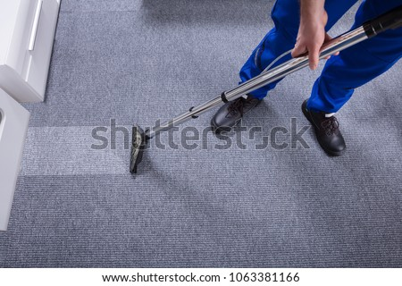 Janitor's Hand Cleaning Carpet With Vacuum Cleaner #1063381166