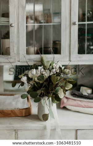 Rustic styled bouquet with green leaves in vase at table in old styled white kitchen cabinet #1063481510