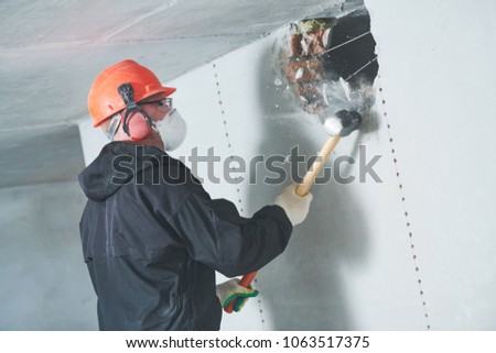 demolition work and rearrangement. worker with sledgehammer destroying wall #1063517375