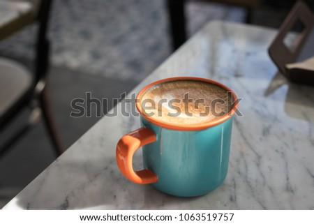 In the cafe : A cup of almond milk cappuccino coffee in orange and blue cup isolated on white table with copy space. #1063519757