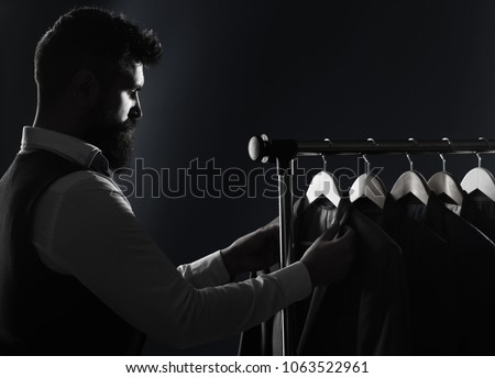 Men clothing, boutiques. Tailor, tailoring. Stylish men's suit. Man suit, tailor in his workshop. Handsome bearded fashion man in classical costume suit. Male suits hanging in a row. Black and white #1063522961