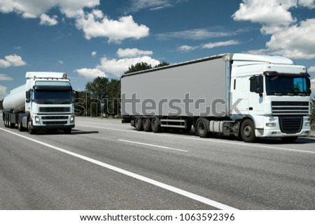 two trucks with container and cistern on road, cargo transportation concept #1063592396
