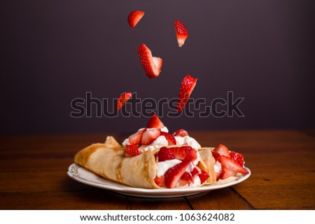 Delicious crepes filled with strawberries and whipped cream with strawberries falling on top of the crepes. Royalty-Free Stock Photo #1063624082