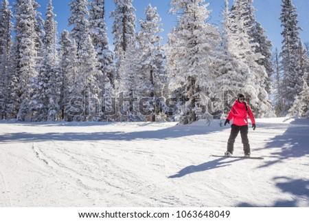 Young woman snowboarder running down the slope in mountains. Winter sport and recreation, leisure outdoor activities. #1063648049