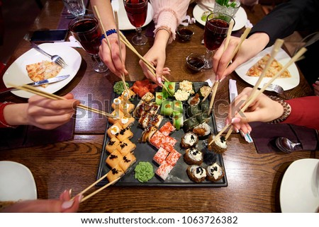 A set of sushi rolls on a table in a restaurant. A party of friends eating sushi rolls using bamboo sticks. #1063726382