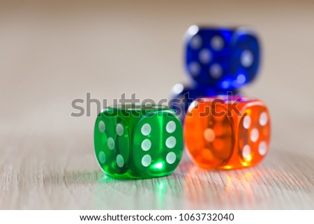 Colourful green, orange and blue gambling dice on table #1063732040
