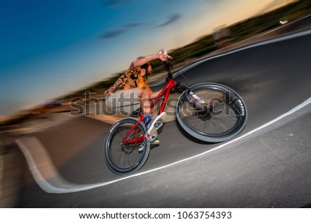 MADRID, SPAIN - AUGUST 10, 2017: A biker rides at a pumptrack during sunset. Motion enhanced with a swipe technique. #1063754393