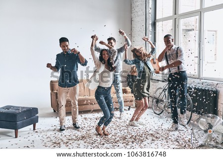 Going crazy. Full length of happy young people dancing while spending time at home with confetti flying everywhere #1063816748
