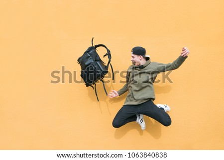 Street young man jumping with a backpack on the background of an orange wall Royalty-Free Stock Photo #1063840838