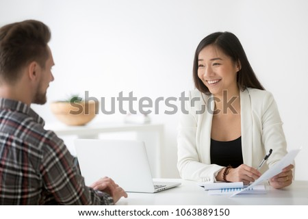 Friendly asian hr smiling laughing talking to candidate at job interview, chinese financial advisor explains customer deal benefit, happy korean businesswoman bank worker consulting client about loan Royalty-Free Stock Photo #1063889150