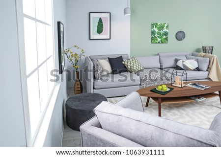 Stylish living room interior with comfortable sofa and table #1063931111