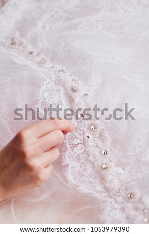 a hand attaching beads on a bridal sache, embroidery on a lace #1063979390