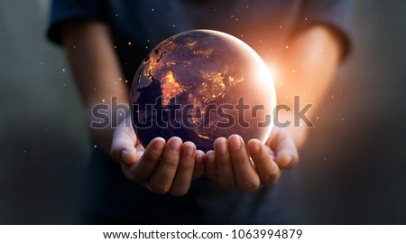 Earth at night was holding in human hands. Earth day. Energy saving concept, Elements of this image furnished by NASA #1063994879