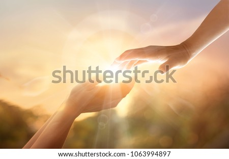 God's helping hand with the white cross on sunset background. Day of remembrance and good friday concept Royalty-Free Stock Photo #1063994897