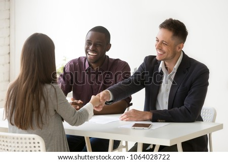 Smiling multiracial hr handshaking female applicant won job interview, friendly diverse executives and successful candidate shaking hands offering employment contract, recruiting and hiring concept Royalty-Free Stock Photo #1064028722