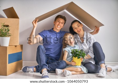 Mother, father and child girl in the house with a symbol of roof. Concept of housing for young family.  #1064050793