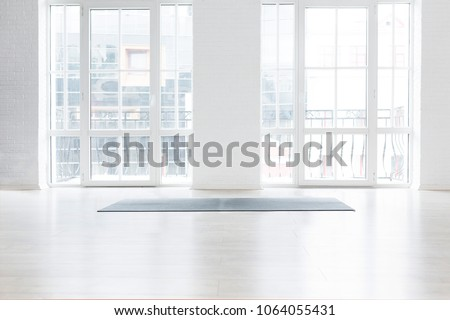 Gym white interior with black yoga mat, big windows, no people. Copy space #1064055431