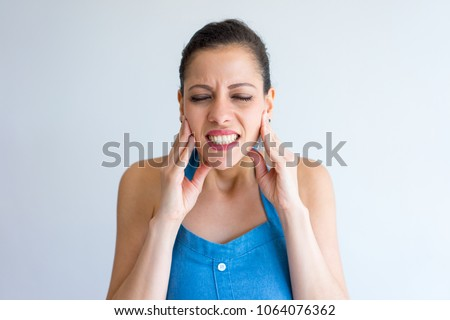 Annoyed young woman suffering from toothache and touching jaw. Irritated girl with closed eyes gritting teeth from pain. Hurt concept #1064076362