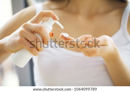 Beauty Face Care. Woman Applying Cream On Skin. #1064099789