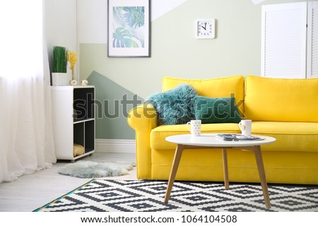 Stylish living room interior with comfortable sofa and table #1064104508