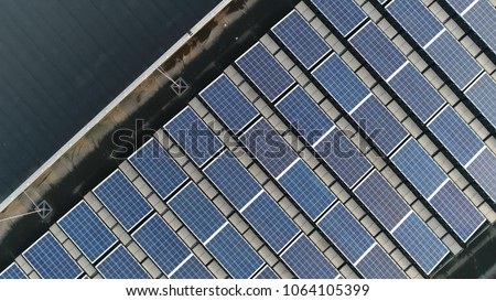 Aerial top down photo of solar panels PV modules mounted on flat roof photovoltaic solar panels absorb sunlight as a source of energy to generate electricity creating sustainable energy Royalty-Free Stock Photo #1064105399