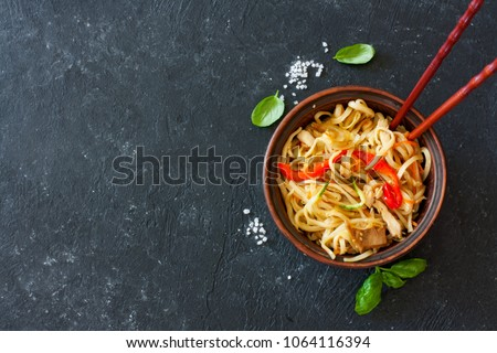 Udon noodles and vegetables served in the clay pot on a black stone background #1064116394