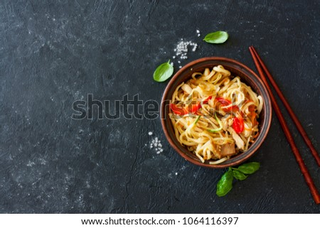 Udon noodles and vegetables served in the clay pot on a black stone background #1064116397